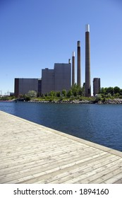 Waterfront coal-powered electric generating station with four smoke stacks.  Boardwalk visible in foreground.
