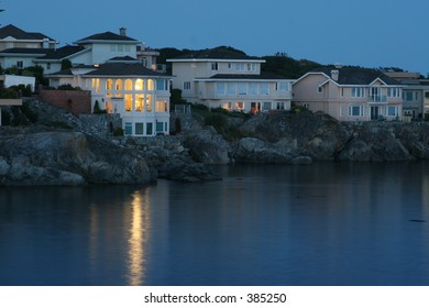 waterfront home lighted at dusk reflected on sheltered cove