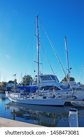 Waterfront marina/dock with berthed boats in tropical water with blue sky backdrop. Safe harbour for sailing and cruising vessels. Tin Can Bay, Queensland, Australia.
