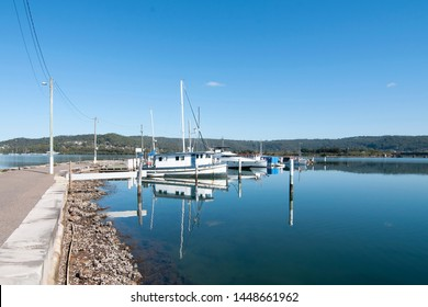 Waterfront marina/dock with boats in glass smooth water with blue sky backdrop. Safe haven for sailing and cruising vessels. Gosford, NSW, Australia.