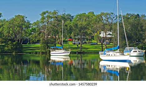 Waterfront maritime dock with moored boats in tropical water with a lush green parkland backdrop and blue sky. Picturesque haven for sailing and cruising vessels. Australia.