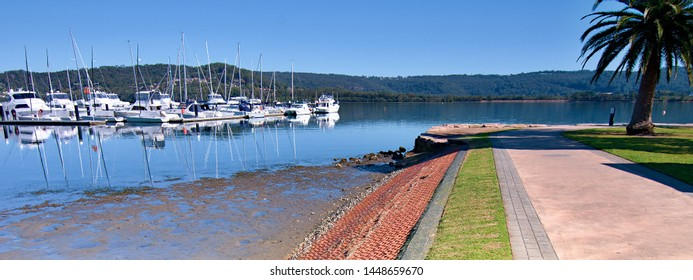 Waterfront park marina/dock panorama landscape with boats, tree covered horizon and a mid blue sky. Safe haven for sailing and cruising vessels. Gosford, Australia.