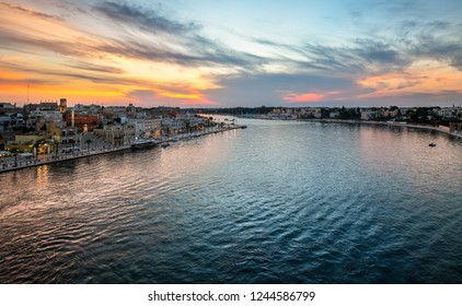 The waterfront promenade fills with tourists enjoying a late summer evening sunset at the port city of Brindisi Italy on the Adriatic Coast in the Puglia region.