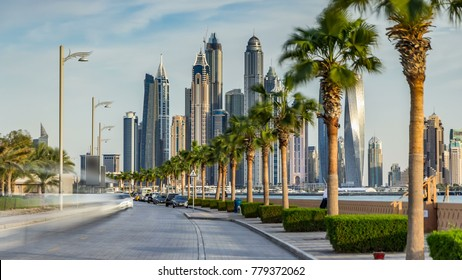 Waterfront promenade on the Palm Jumeirah with palms at road and traffic timelapse before sunset. Dubai, United Arab Emirates. Dubai marina towers on background