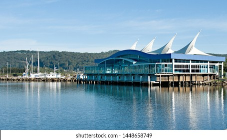 Waterfront public marina/dock and breakwall with boats, restaraunt and tree covered horizon with a pale blue sky. Safe haven for sailing and cruising vessels. Gosford, Australia.