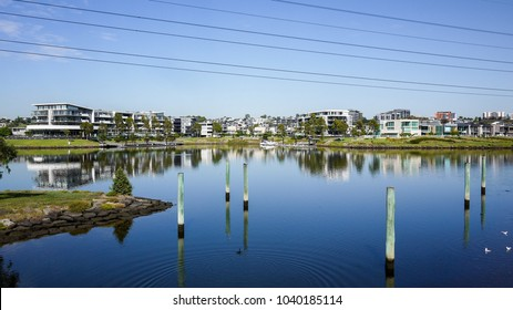 Waterfront suburban modern apartment buildings against blue sky and green grass. Brand new luxury houses at the riverbank of Maribyrnong River of Melbourne.