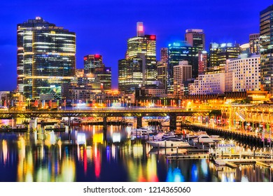 Waterfront of Sydney city CBD high-rise towers around Darling harbour with marina boats over Pyrmont bridge reflecting in still waters at sunset.