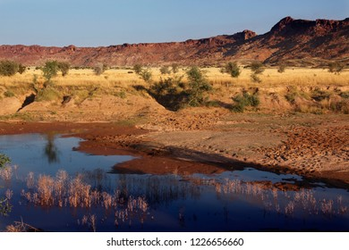 Waterhole in the arid landscape of Damaraland near Twyfelfonaine in the north of Namibia.