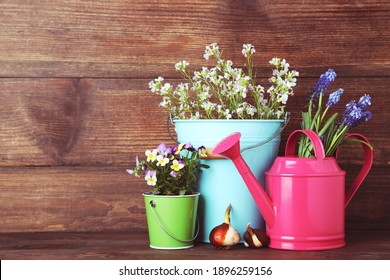 Watering can with flowers in buckets on wooden table
