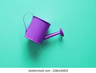 Watering can on colorful background.