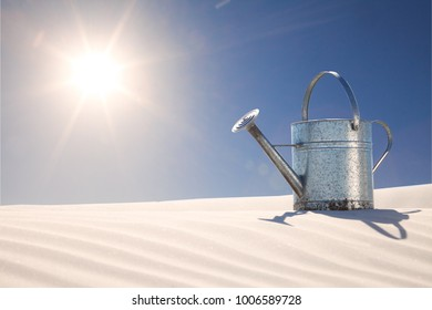watering can on desert sand dune as concept for climate change,drought and water restrictions