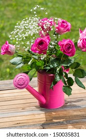 Watering can with roses bouquet