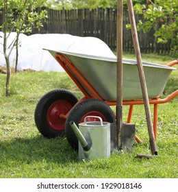 watering can, a shovel, a rake and a garden wheelbarrow against the backdrop of a garden and a vegetable garden. summer work tool