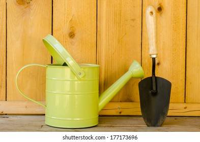 Watering can and trowel on wood background.