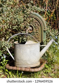 Watering can in zinc on a fountain in cast iron in a garden during spring