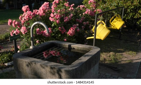 """Watering cans by a well for public use by visitors at a German cemetery. Sign says """"Not Drinking Water"""""""