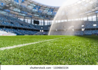 Watering the football field. Close-up macro shot on green grass with white stripe.