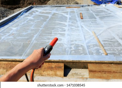 Watering fresh concrete slab using a hose. The wet concrete is additionally kept moist with a plastic foil.