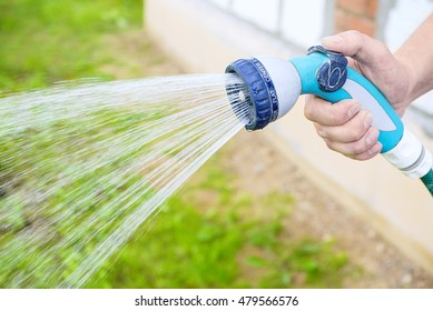 Watering the garden with a watering can, holds the sprinkler hose for irrigation plants. Gardener with watering hose and sprayer water on the vegetable