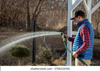 Watering garden equipment - hand holds the sprinkler hose for irrigation plants. Gardener with watering hose and sprayer water on the vegetable.