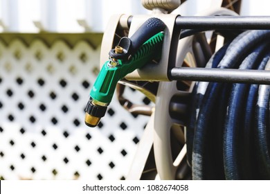 Watering garden equipment, garden hose storage and pistol nozzle. Garden hose pistol on background of spring or summer backyard. Modern water hose storage on backyard. Garden pistol with jet spray.