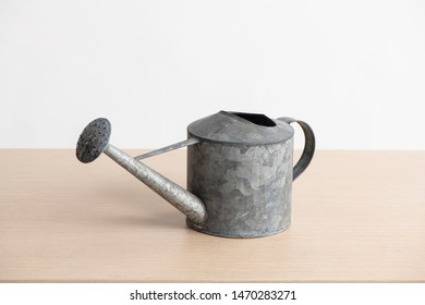 watering pot on wooden table and white background
