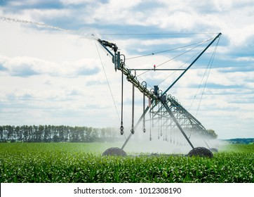Watering system in the field. An irrigation pivot watering a field