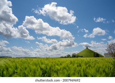 Waterloo, Belgium - May 24 2021 : Butte de Lion monument on a sunny yet cloudy day with green meadow and corn fields in the foreground