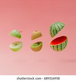 Watermelon, apple and kiwi sliced on pastel pink background. Minimal fruit concept.