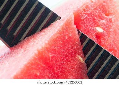 Watermelon close up: Black knife slicing a watermelon. With summer arriving, watermelon is a delicious fruit to eat.