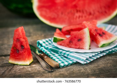 Watermelon cuts with cutlery on wooden table