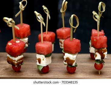Watermelon Feta Salad Hors d'oeuvres made with watermelon, feta cheese, balsamic vinegar, leaf of lettuce, cherry tomato with hors d'oeuvre pick on wood cutting board