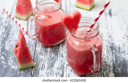 Watermelon fresh in glass jars of masons, slices of watermelon on a gray background