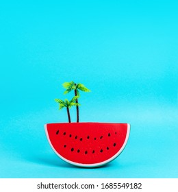 Watermelon fruit with palm tree plastic toy on pastel blue background. Creative minimal summer concept.