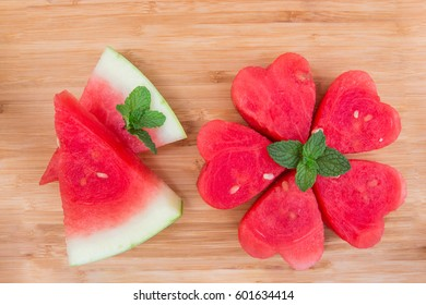 Watermelon heart shaped and decorate mint on wooden background.