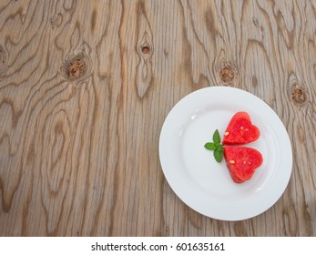 Watermelon heart shaped and decorate mint on white plate and wooden background.