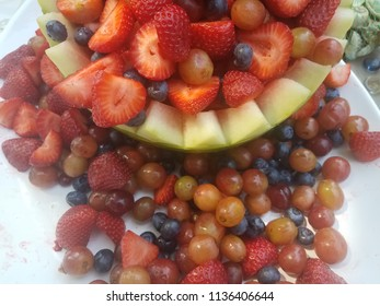 watermelon hollowed out with blueberries, strawberries and grapes inside