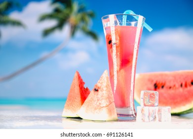 Watermelon ice cold drink on a beach with palms