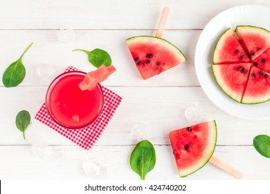 Watermelon juice, watermelon slices and spinach leaves. Top view, flat lay