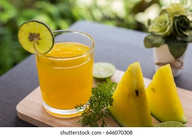 Watermelon juice with yellow pulp with lime and fresh sliced of watermelon on wooden plate with gray tablecloth and green nature background. Select focus.