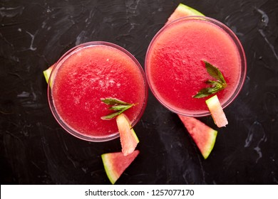 Watermelon margarita cocktail on black background. Fresh watermelon lemonade with mint and  ice for summer party. Refreshing summer drink. Top view.