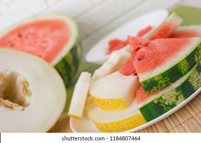 Watermelon and melon slices on cutting board against light background