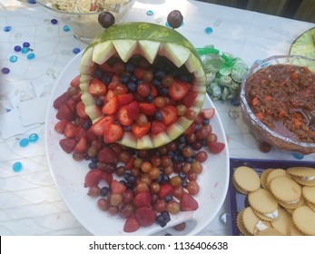 watermelon monster face with teeth and blueberries, strawberries and grapes in the mouth