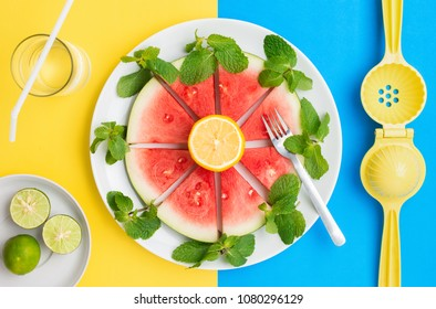 Watermelon on plate with lemon and mint leaves on a split contrasting color background.