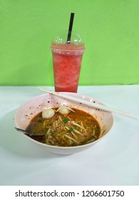 Watermelon on smooth color, healthy drink menu with Noodles in Thai spicy Tom yum soup with pork. There are on the table. Delicious taste all two menu.
