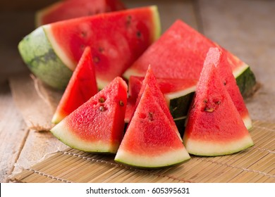 watermelon and watermelon pieces in a wooden background.