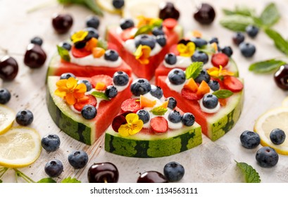 Watermelon pizza with addition of blueberries, strawberries, natural yogurt and edible flowers. Delicious and healthy summer dessert