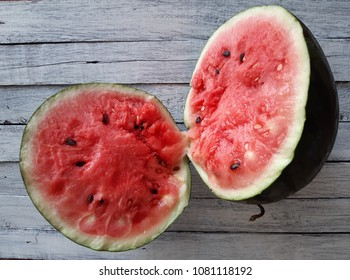 Watermelon is placed on a white wooden floor.
