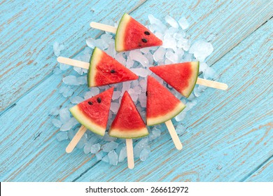 watermelon popsicle yummy fresh summer fruit sweet dessert on vintage old wood teak blue flat lay