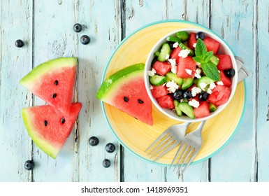 Watermelon salad with cucumber, blueberries and feta cheese. Overhead view table scene on a blue wood background.